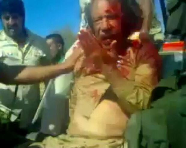 Sur cet extrait d'une vidéo filmée avec un mobile, Kadhafi, malmené par les rebelles, saigne abondamment. Il ne lui reste que quelques instants à vivre.