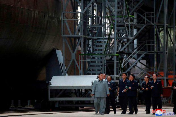 Kim Jong-un et la délégation visitant une usine où est fabriqué un sous-marin.