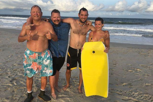 Kimberly Goricki sort de l'eau avec son surf. Avec elle, son frère, son père et un ami.