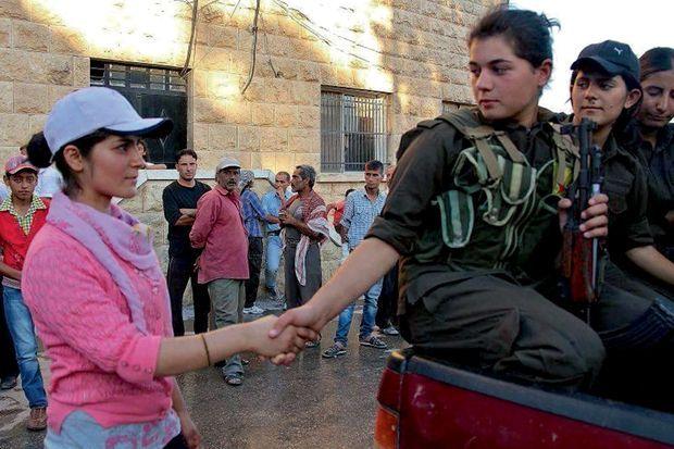 Une très jeune combattante dit adieu à sa sœur. Dans certains secteurs, les femmes constituent 30 % des effectifs.