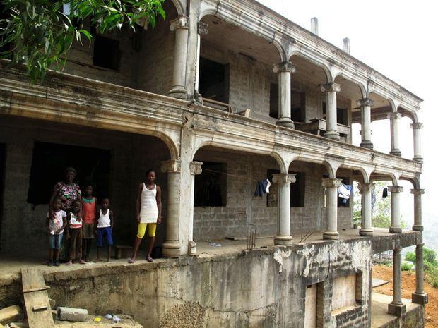 Ci-contre : à Regent, Konnah Mansallay (à g.) et ses enfants cohabitent dans cette maison en construction, en attendant mieux.