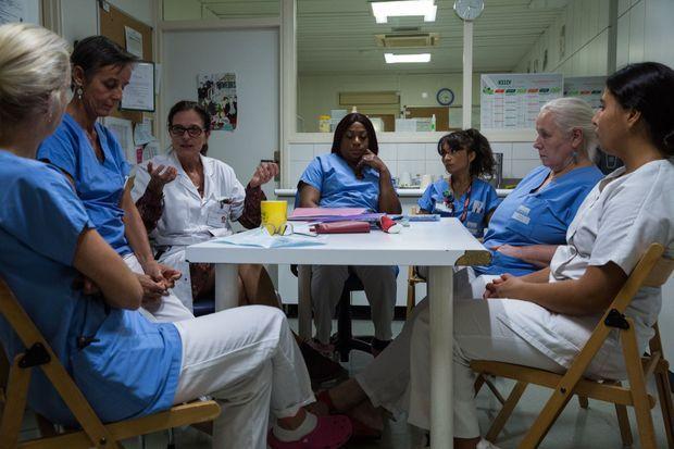Réunion de transmission entre deux équipes de médecins, infirmières et aide-soignantes. Chaque patient est évoqué.