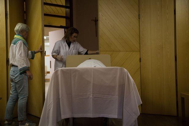 Aider jusqu'au bout. Le corps d'un défunt et transporté dans une des 3 salles de présentation aux familles.