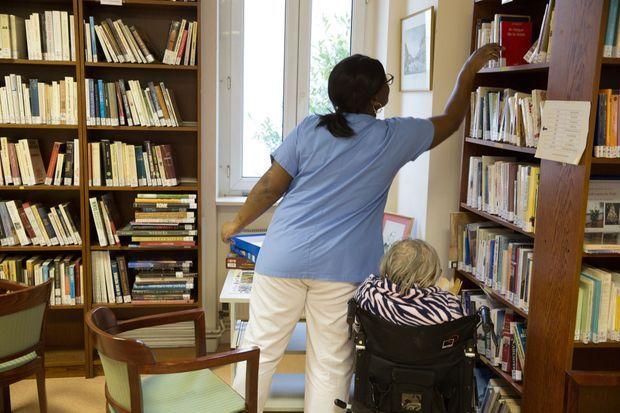 Favoriser les liens. Une aide soignante accompagne une patiente à la bibliothèque où l'on peut aussi organiser une fête familiale