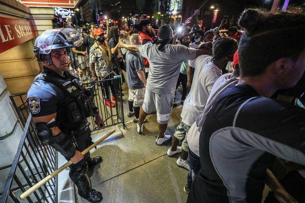L'agent Hinshaw, piégé contre un mur et protégé par des manifestants.