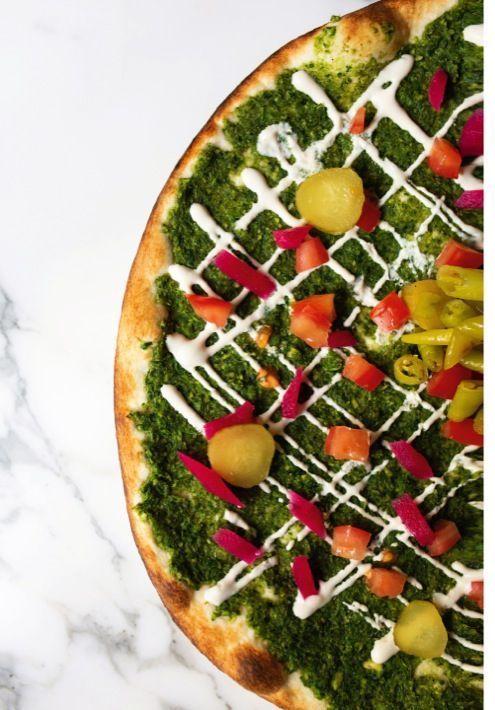 La Mann'oushe Falafel avec fèves, coriandre, tahini, tomates, navets et concombres en pickles.