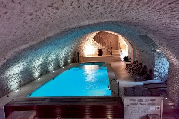 La piscine creusée sous une voûte de pierre.