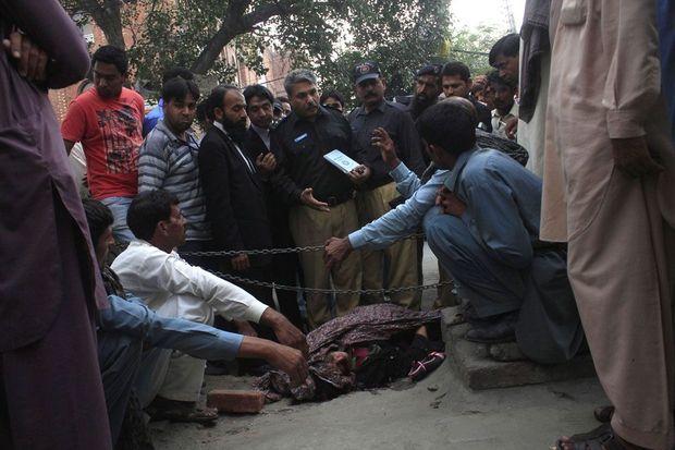 Mardi 27 mai, à Lahore, au Pakistan, des policiers protègent le corps de Farzana Parveen, enceinte de trois mois. Sa famille vient de la tuer à coups de briques pour s'être mariée sans son accord.