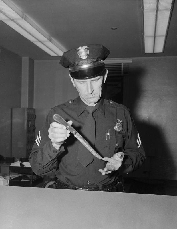 Le sergent de police Russel R. Peterson examine le couteau qui a tué Johnny Stompanato, dans la nuit du 4 au 5 avril 1958.