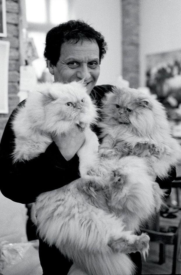 Le couturier et deux de ses chats chez lui, à Paris, en 1998