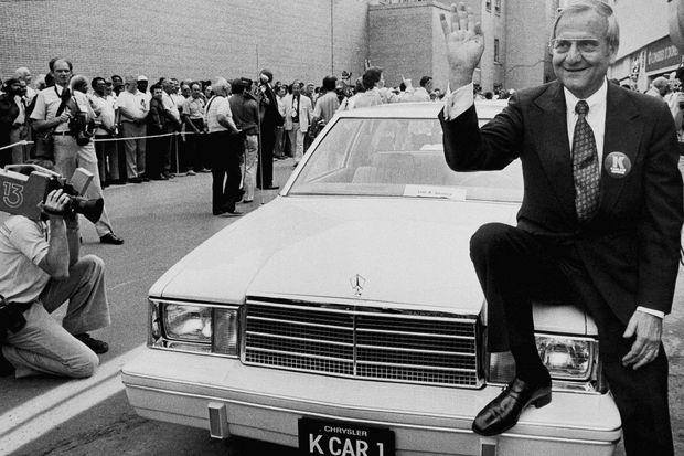 Août 1980, Lee Iacocca pose sur le capot d'une Plymouth Reliant, premier modèle de la plateforme K, plus compacte et économique, introduite par le groupe Chrysler.
