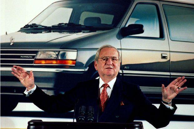 Lee Iacocca présente les résultats de Chrysler devant une photo représentant le Voyager, monospace à succès du groupe.