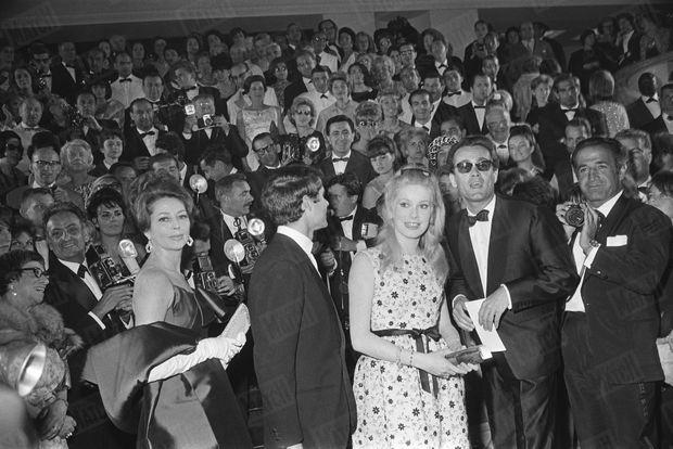"""Michel Legrand avec Catherine Deneuve lors de la consécration à Cannes des """"Parapluies de Cherbourg"""", au 17ème Festival de Cannes en mai 1964."""