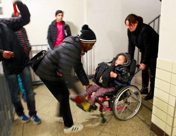 Les ados, qui écoutent de la musique dans le hall, aident une maman à monter le fauteuil de sa fille handicapée.