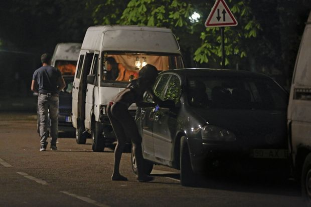 Les clients se garent entre les camionnettes alignées. Certaines prostituées sortent de leur véhicule pour négocier.