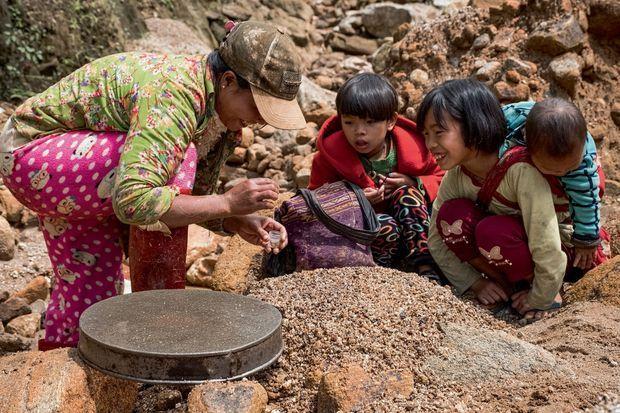 Les femmes, interdites à la mine, tamisent les restes.