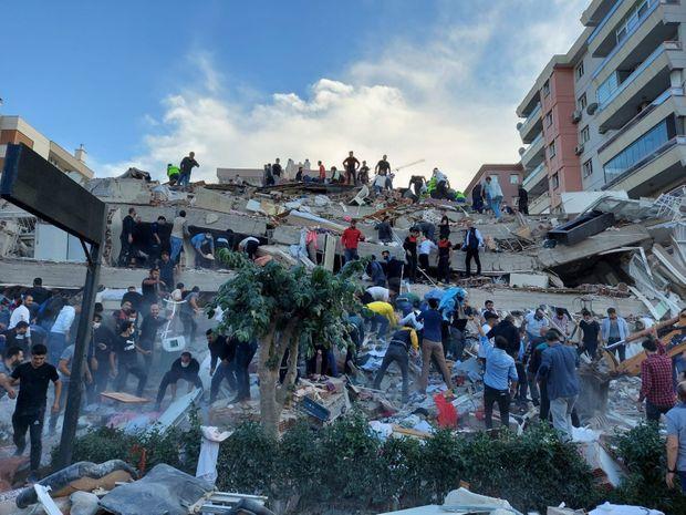 Les habitants et les responsables recherchent des survivants dans un bâtiment effondré à Izmir