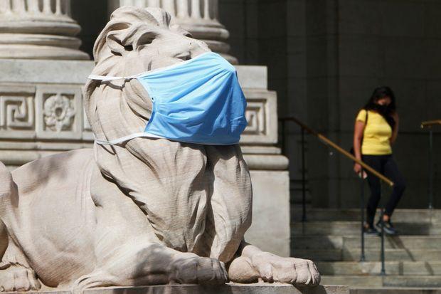 Un masque appliqué sur une statue de lion à la bibliothèque publique de New York.