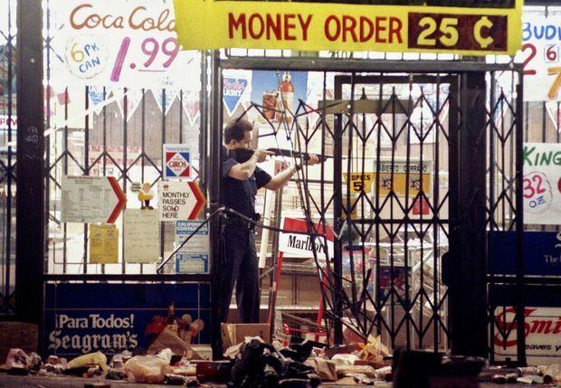 De son fusil à pompe, un policier tient en joue des pillards, lors des émeutes de Los Angeles, le 30 avril 1992.