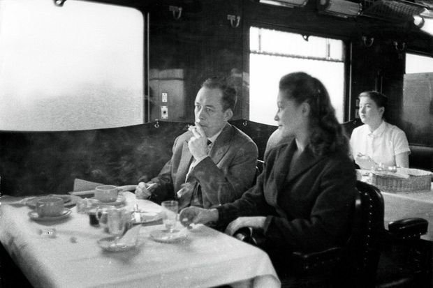 Albert Camus, prix Nobel de littérature en 1957 pour l'ensemble de son oeuvre, part en Suède en train pour recevoir le prix : l'écrivain fumant une cigarette assis à une table du wagon restaurant aux côtés de Janine Gallimard.