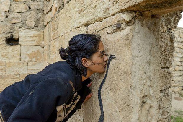 Fryal, 18 ans, embrasse le serpent noir, symbole de la sagesse, au temple de Zewa Name Sivan, un lieu saint yézidi, le 15 novembre. Emprisonnée à Kotcho, elle a assisté à des ventes de femmes. La plus jeune avait 8 ans.