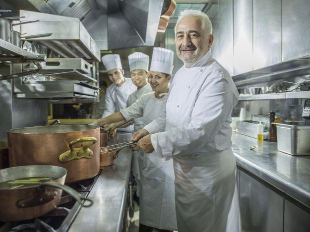 Guy Savoy dans les cuisines de son restaurant parisien, avec ses seconds.