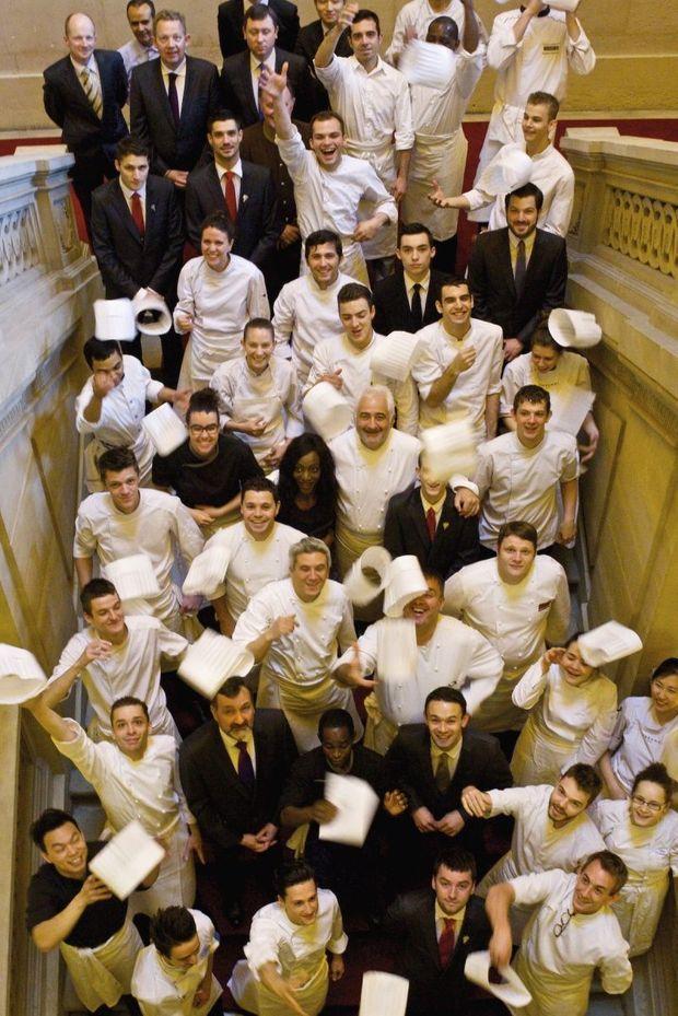 Guy Savoy au milieu de son équipe, dans l'escalier monumental de l'hôtel.