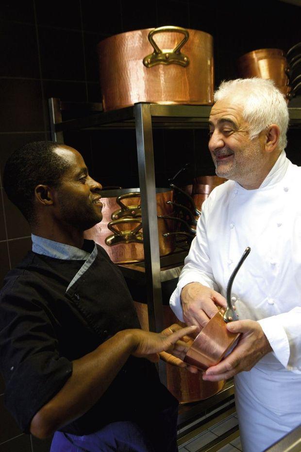 Guy Savoy devant sa collection de casseroles en cuivre martelées à la main