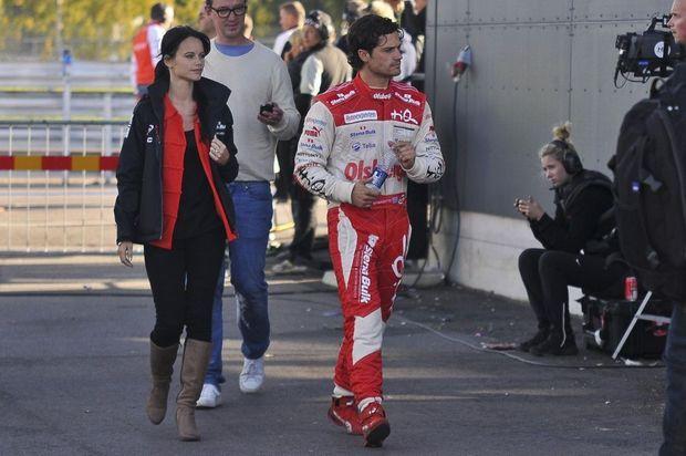 Le prince en combinaison de pilote automobile, suivi de Sofia, lors d'une épreuve de la Porsche Carrera Cup, à Mantorp, en Suède, le 24 septembre 2011.