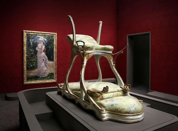 Un instrument de félicité dont le mode d'emploi est laissé à l'imagination. Derrière, un tableau d'Henri Gervex représente Valtesse de La Bigne (en médaillon). Cette célèbre cocotte a ruiné de nombreux amants. Parmi ses conquêtes, Napoléon III.