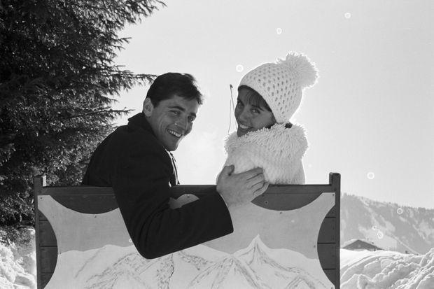 Le 25 janvier 1963, en France, à Megeve, le jour de leur mariage, après la cérémonie , le chanteur français Sacha DISTEL et la championne de ski Francine BREAUD, dans la neige posant souriants, de dos, assis dans un traineau la tête tournée vers l'objectif.
