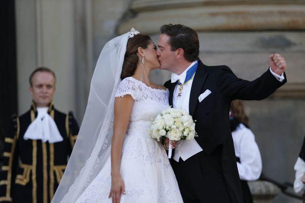 Après la messe, devant le château, Chris lève un poing triomphant en embrassant sa femme.