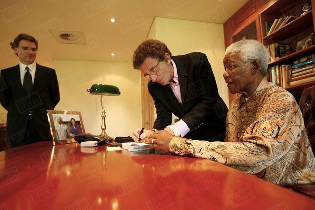 """Olivier Royant, directeur de la rédaction de Paris Match observe Nelson Mandela, assis dans le bureau de sa fondation à Johannesburg, en compagnie de Jack Lang dédicaçant le livre qu'il lui a consacré, """"Nelson Mandela, leçon de vie pour l'avenir"""" (Éd. Perrin), en février 2006."""