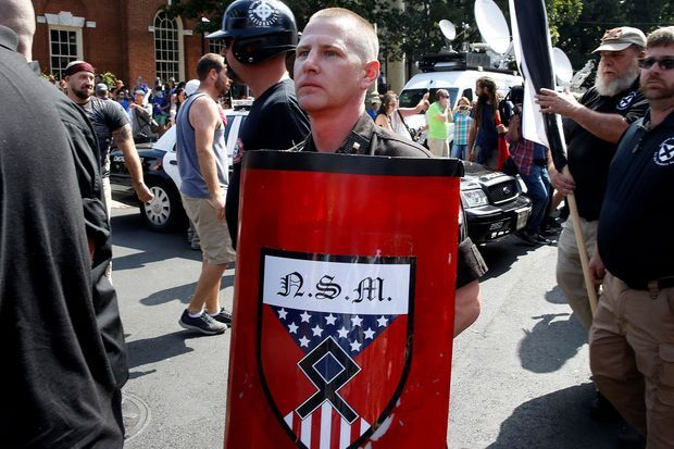 Le bouclier de ce manifestant raciste arbore l'Odal, une rune symbole du National Socialist Movement. Le NSM préfère depuis 2016 ce symbole aux croix gammées qui avaient autrefois ses faveurs. La rune a été utilisée durant la Seconde Guerre mondiale par des divisions Waffen-SS.