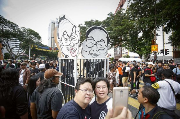Manifestation à Kuala Lumpur, le 27 août, pour l'arrestation de Najib Razak : le Premier ministre malaisien, mêlé au scandale financier, est représenté « emprisonné » avec Jho Low.