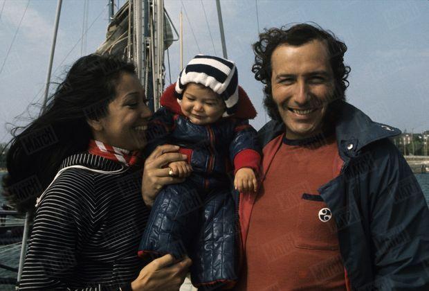 """Alain Colas et son épouse Teura posent avec leur fille Vaïmiti à la proue du """"Manureva"""", en mai 1975."""