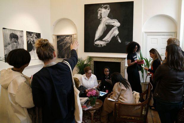 La galeriste française Mariane Ibrahim (assise au centre) dans l'espace dédié à sa galerie au 1:54, le 6 octobre 2016. Derrière elle, une oeuvre du couple d'artistes Mwangi Hutter
