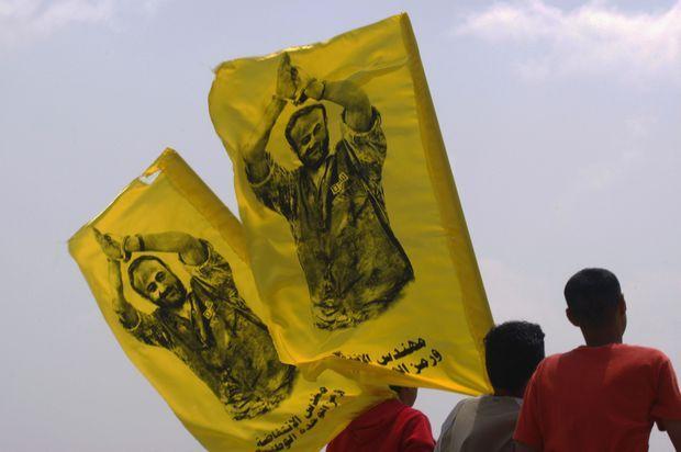 Des Palestiniens brandissent des drapeaux à l'effigie de Marwan Barghouti.