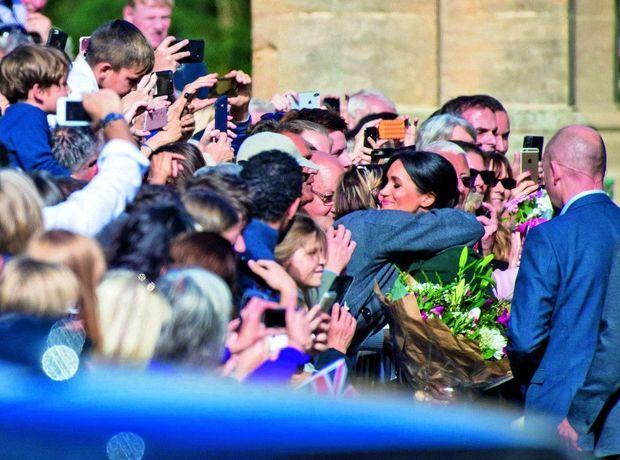 A l'américaine. Le 3 octobre, lors d'une visite dans le comté de Sussex, Meghan se laisse enlacer par une fan.