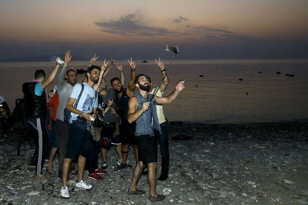 Arrivés sur la terre ferme de l'île de Kos, le 9 août, ces Syriens se prennent en photo.
