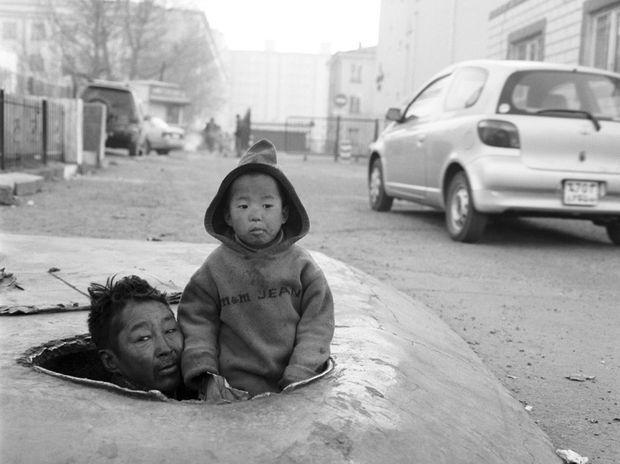 Scène de la misère en Mongolie, par Richard Aujard. A Oulan-Bator, d'anciens paysans ruinés, des sans-logis, des vagabonds, des ados vivent sous terre dans les canalisations d'eau chaude. Ici, Narangeret et son fils de 4 ans, Saikhnaa.