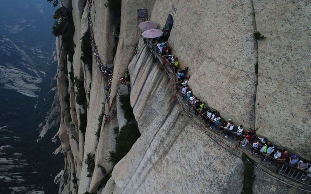 MONTAGNE SACRÉE DU TAOÏSME A la queue leu leu sur une passerelle de planches accrochée au mont Huashan. Avec 1 500 mètres de vide à côté de ses pieds. Et la possibilité d'acheter sa photo imprimée et plastifiée sur place…