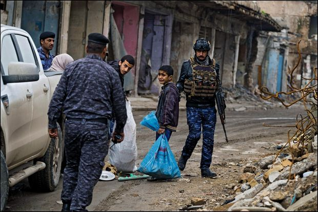 La police irakienne arrête un garçon pour vérifier s'il ne s'est pas livré au pillage. Il sera relâché peu après.