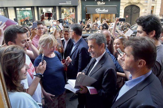 Pour Nicolas Sarkozy, la séance de dédicaces continue dans la rue. Vendredi 28 juin, à la sortie de la librairie Lamartine, Paris XVIe.