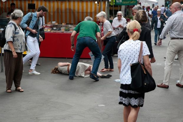 NKM est à terre, son agresseur (à droite, en pantalon beige) regarde vers elle
