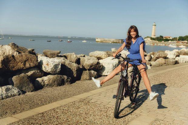 Ophélie fait une démonstration de roue libre sans les pieds, devant le phare de Vallières.