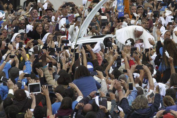 Bain de foule et de portables pour le Souverain Pontife qui embrasse un bébé alors qu'il quitte le Sanctuaire de Fatima. Bain de foule et de portables pour le Souverain Pontife qui embrasse un bébé alors qu'il quitte le Sanctuaire de Fatima, le lendemain.