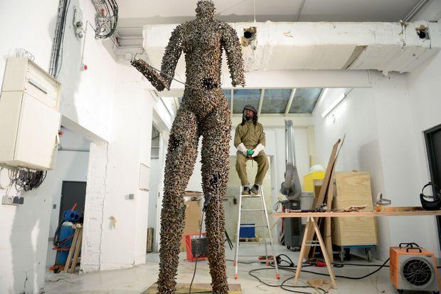 Pendant le montage de « Porteuse de vies », sa sculpture d'une femme de plus de 4 mètres, en douilles.