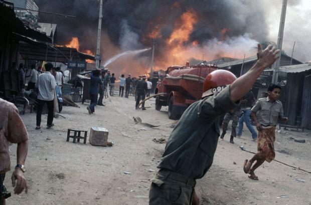 Des soldats tentent d'éteindre un incendie à Phnom Penh lors de combats contre les Khmers rouges en avril 1975.