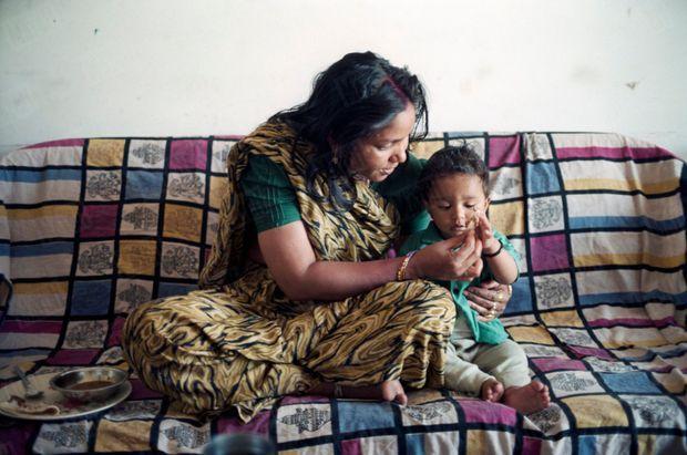 Phoolan Devi, la justicière en sari, publie ses mémoires et reçoit en exclusivité Paris Match dans son appartement de Gulmohar Park à Delhi, en mars 1996. Elle pose, souriante, son petit neveu Laloo assis à ses côtés sur un canapé.